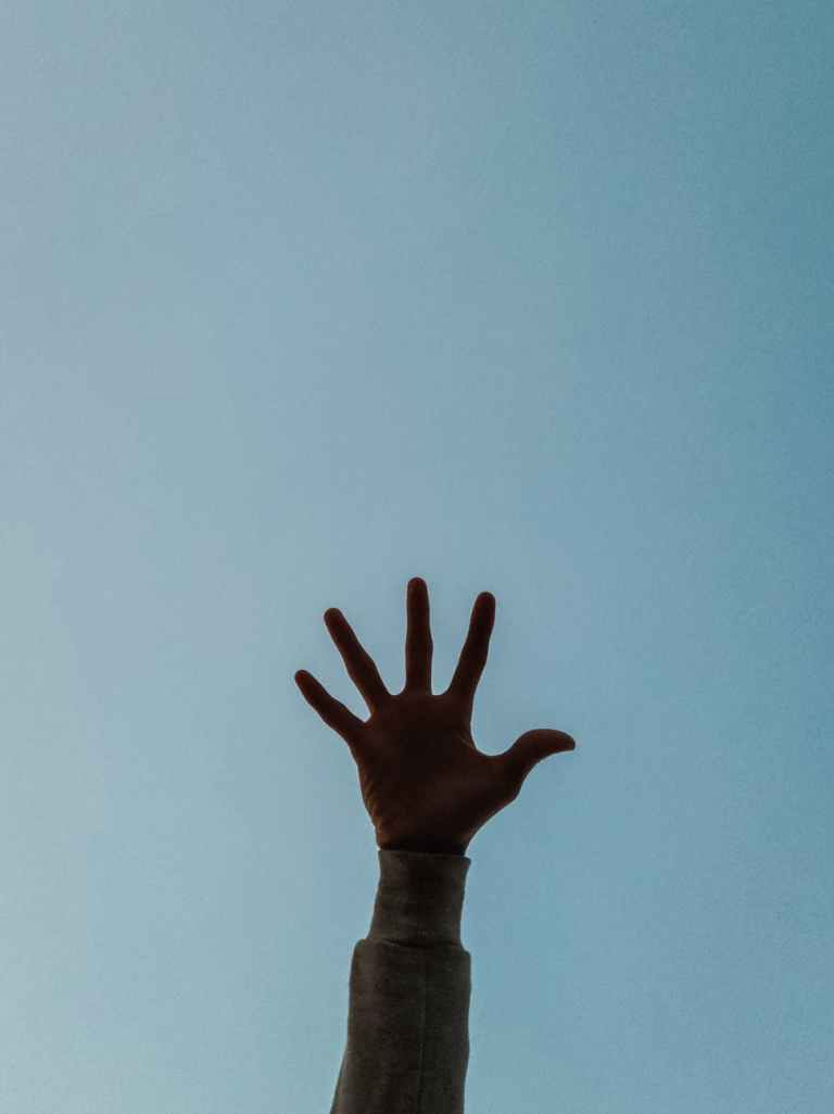 person s hand raised in the air